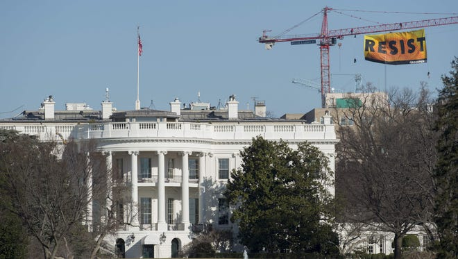 """Greenpeace protesters unfurl a banner reading """"Resist"""" from atop a construction crane behind the White House on Jan. 25, 2017 in Washington, D.C."""