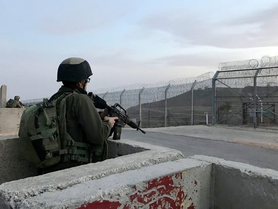An Israeli soldier waits at the Syrian border before