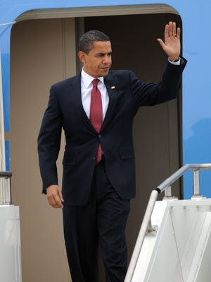 President Barack Obama waves as he walks off Air Force One upon his arrival at Michiana Regional Airport in South Bend, Ind., Feb. 9, 2009. Obama held a town hall meeting in Elkhart in 2009 and is returning today for a similar event.
