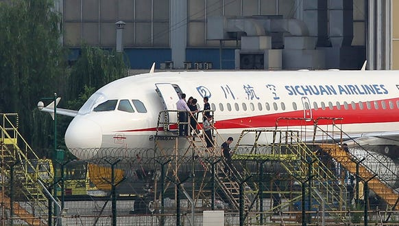Sichuan Airlines employees check an Airbus A319 on