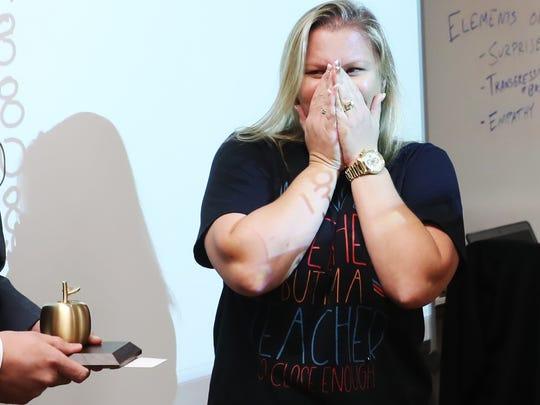 Island Coast High School algebra teacher Samantha Hutchinson reacts to winning the Golden Apple on Friday.