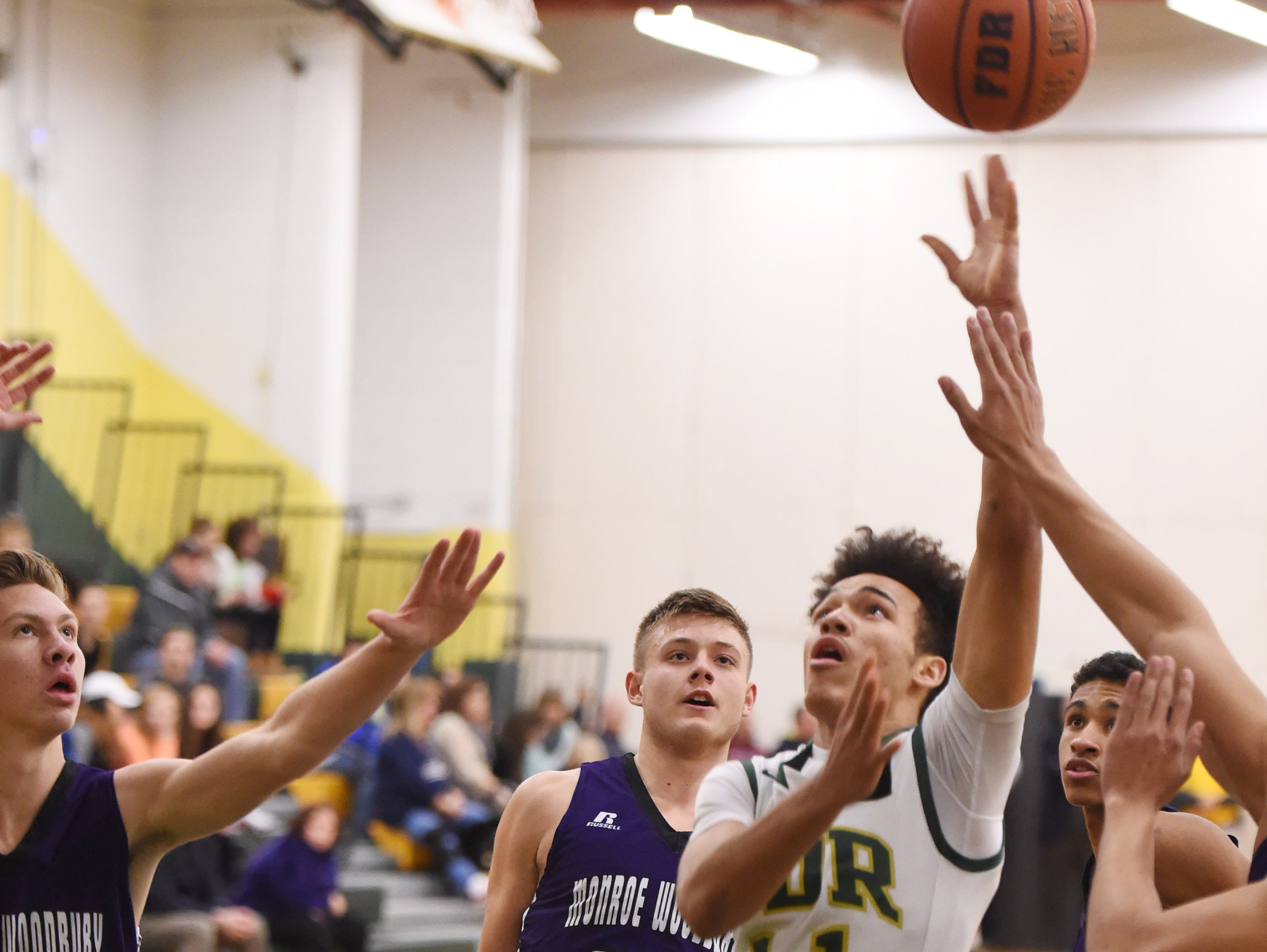 FDR's Nowah Rosado shoots over Monroe Woodbury's , from left, Johnny McCormick and Patrick Feeley during Monday's game in Hyde Park.