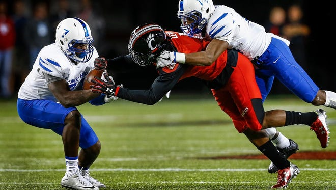 University of Memphis defender Curtis Akins (left) grabs an interception away from University of Cincinnati receiver Kahlil Lewis (middle) with the help of teammate Chris Morley (right) during first quarter action in Cincinnati, Ohio. The interception lead to a Tigers' first touchdown on the next series.