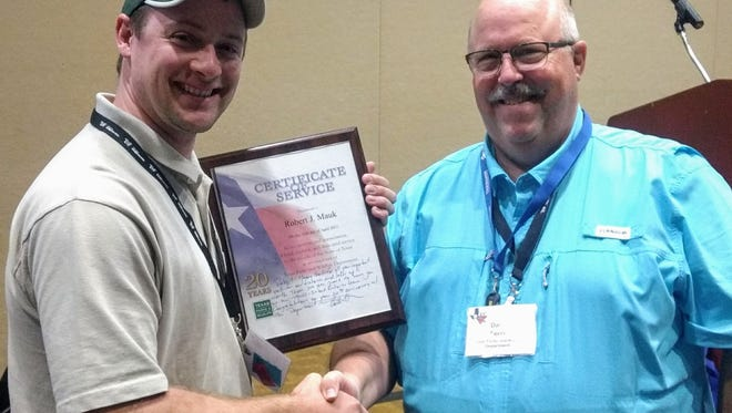 At the recent Texas Chapter of the American Fisheries Society Annual meeting in College Station, Texas Parks and Wildlife Department Inland Fisheries Biologist Robert Mauk received recognition for 20 years of service to the Department. All of Mauk's 20 years have been spent in the Wichita Falls District office. Pictured is Wichita Falls District Technician Ben Yeager accepting the service plaque and pin from TPWD Fisheries Chief Dave Terre on Mauk's behalf.