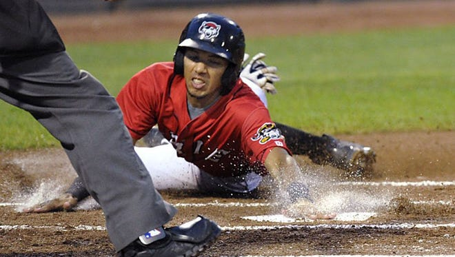 Erie SeaWolves baserunner Dixon Machado, left, slides safely into home to score against the Bowie Baysox on Aug. 26, 2014.