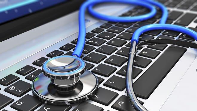 Detail of stethoscope on laptop keyboard.