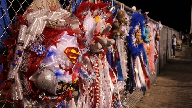 A Batman vs. Superman homecoming mum hangs from a fence at Irvin High School on Friday night, Sept. 23.