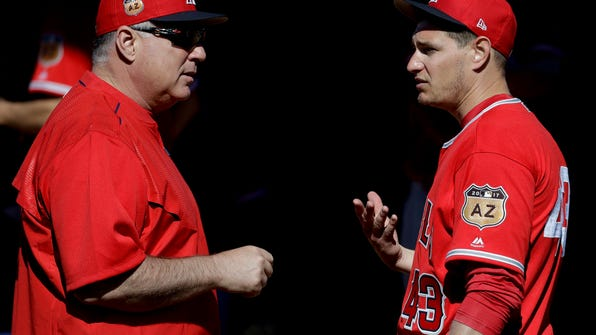 Los Angeles Angels manager Mike Scioscia, left, talks with starting pitcher Garrett Richards during spring baseball practice in Tempe, Ariz., Wednesday, Feb. 15, 2017. (AP Photo/Chris Carlson)