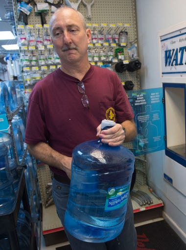 """Tom Morrissey, of Palm City, filled two large water jugs in preparation for Hurricane Irma on Monday, Sept. 4, 2017 at Peter's Hardware Center in Palm City. """"This is not our first rodeo,"""" said store owner Peter Wernick, who has been collecting hurricane supply inventory for years and says the most popular hurricane items he sells are propane, batteries, flashlights, rope and straps, tarps, nut and bolts and water. Peter's Hardware was busier than normal and expected to sell out the Monday propane supply by noon. """"I think last year's storm brought to everyone's mind how underprepared we were. With Harvey last week, I think it brought attention as well."""""""