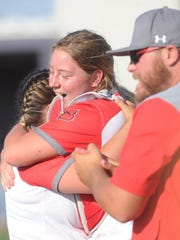 Hermleigh catcher Sandra Carr hugs pitcher Morgan Kariainen after the Lady Cardinals beat Rotan 17-8 in a one-game Region I-1A semifinal playoff Saturdy at ACU's Wells Field. Kariainen's father died May 7.