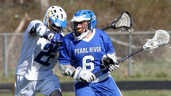North Salem's Mike Rajazzino checks Pearl River's James Stephen during a boys lacrosse match at North Salem High School April 13, 2013. Pearl River defeated North Salem 10-9 in triple OT.(Matthew Brown/The Journal News)