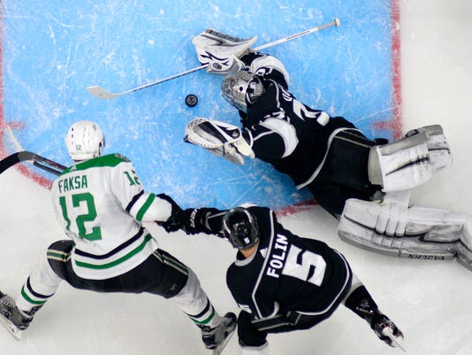 Los Angeles Kings goaltender Jonathan Quick, right, stops a shot by Dallas Stars center Radek Faksa, left, of the Czech Republic, as defenseman Christian Folin, of Sweden, helps Quick during the second period of an NHL hockey game Thursday, Feb. 22, 2018, in Los Angeles. (AP Photo/Mark J. Terrill)
