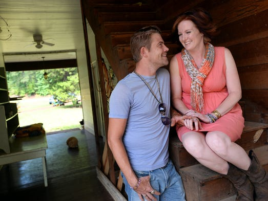 Chris Parker and Jackie Lewis sit in the breezeway of the 1888 two-story dogtrot home that they are renovating in rural Bienville Parish.