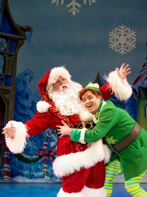 "Santa (Ken Clement) endures a hug from Buddy (Sam Hartley) in ""Elf the Musical."""