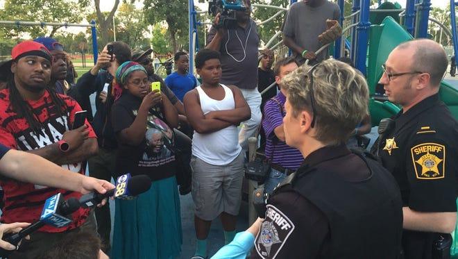 Milwaukee County sheriff's deputies talk to residents at Sherman Park on Sunday evening.