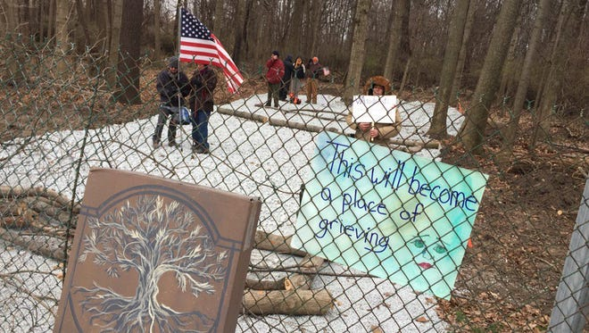 Protestors block the construction entrance to the VA section of Crown Hill cemetery with tree limbs on Monday.