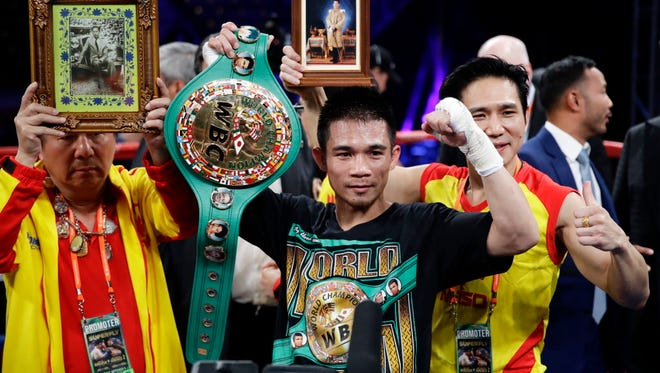 Srisaket Sor Rungvisai poses for photos after knocking out Roman Gonzalez during the fourth round of the WBC super flyweight championship boxing match.