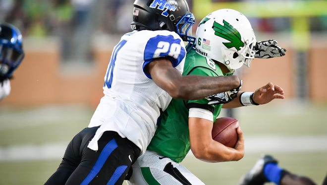 Middle Tennessee senior cornerback Dontavious Heard (28) sacks North Texas freshman quarter back Mason Fine  (6), Saturday, October 1, 2016, in Denton, Texas.