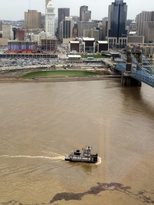 Debris washed from tributaries into the Ohio River by heavy rain drifts past the tow boat Mac McGinnis as she pushes upriver near the Roebling Suspension Bridge.