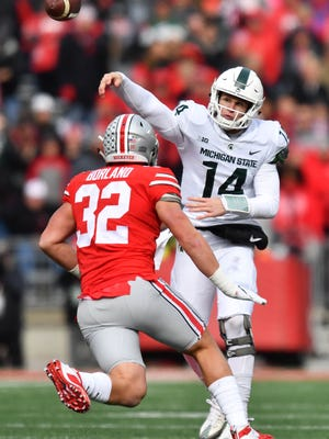 Quarterback Brian Lewerke #14 of the Michigan State Spartans passes in the first quarter as Tuf Borland #32 of the Ohio State Buckeyes closes in to defend at Ohio Stadium on November 11, 2017 in Columbus, Ohio.