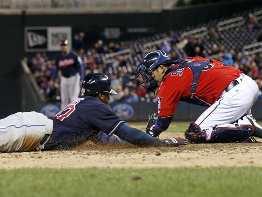 Cleveland Indians' Rajai Davis, left, slides safely into home to score on a Jason Kipnis single as Minnesota Twins catcher Kurt Suzuki makes the tag minus the ball in the fifth inning of a baseball game Monday, April 25, 2016, in Minneapolis. (AP Photo/Jim Mone)