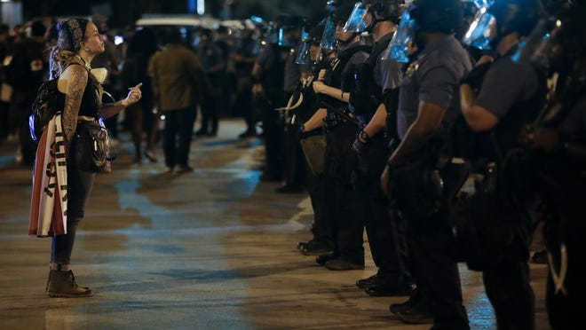 A protester confronts a line of police in riot gear near midnight Wednesday night, June 3, 2020, in Kansas City, Mo., after a unity march to protest against police brutality following the death of George Floyd, who died after being restrained by Minneapolis police officers on May 25.