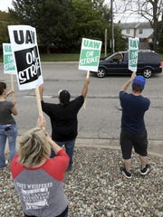 Members of UAW Local 598 wave to passing cars honking in support on Van Slyke Road in front of the General Motors Flint Assembly plant in Flint, Michigan on Sunday, September 15, 2019. The United Auto Workers union announced Sunday that its workers at General Motors plants in the U.S. would go on strike just before midnight because contentious talks on a new contract had broken down. (Eric Seals/Star Tribune via AP)