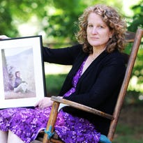 Cindy McMahon, an author and Buncombe County school board member, holds a picture of her mother, Carol, at her home in Haw Creek..