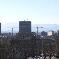 Cranes rise over downtown Asheville construction projects, including new hotels.