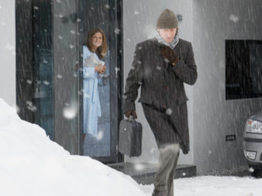 Man leaving house in snow, woman standing at front door, smiling