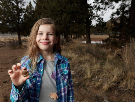 Naomi Vaughan, 7, holds an ammonite fossil near the