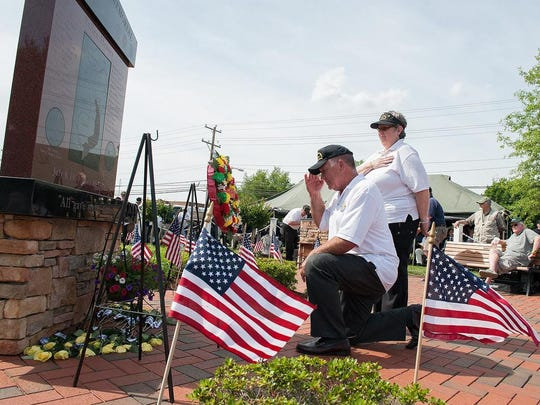"Joseph Startt Jr., president, and Kathy Steele, associate president with the Vietnam Veterans of America, lay a wreath at the dedication of the UH-1 ""Huey"" helicopter at the 2014 Memorial Day Ceremony by the Kent County Chapter 850, Vietnam Veterans of America."
