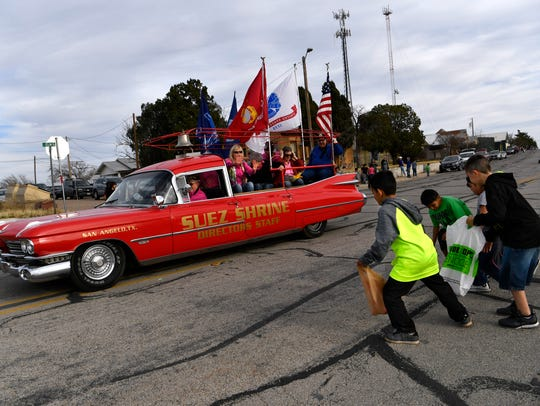 Children scramble for candy as a converted hearse carrying Shriners passes during the parade Thursday for the World's Largest Rattlesnake Roundup in Sweetwater.