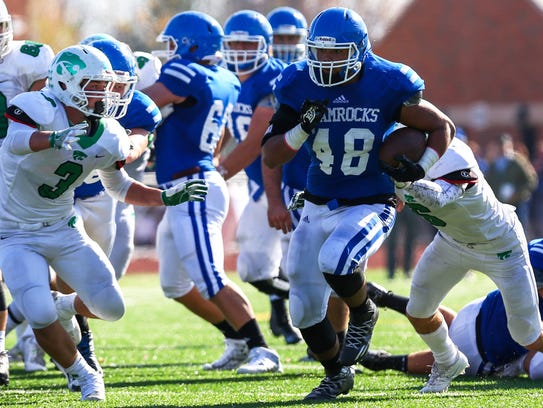 Catholic Central's Matt Young (48) slips through Novi
