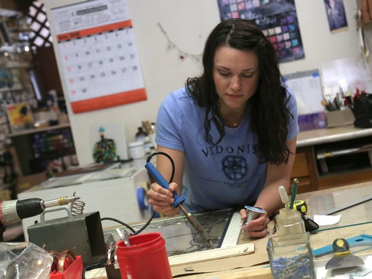 Tiffany Vidonish-Knell solders a joint in the workspace at Vidonish Stained Glass Studios in Lexington.