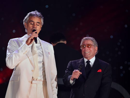 Andrea Bocelli sings as Tony Bennett looks on during a New York Philharmonic concert in Central Park.