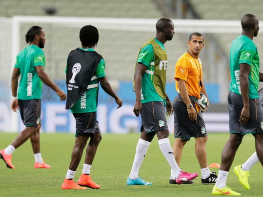 Ivory Coast's head coach Sabri Lamouche, second right, speaks with Yaya Toure, center, during on official training session the day before the group C World Cup soccer match between Greece and Ivory Coast at the Arena Castelao in Fortaleza, Brazil, Monday, June 23, 2014. (AP Photo/Fernando Llano)