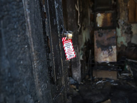 An evidence tag hangs on a door Tuesday at a burned-out
