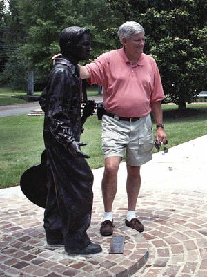 Tourist Jerry Morrison takes a photo with the statue of Elvis Presley at age 13 near his birthplace in Tupelo, Miss.