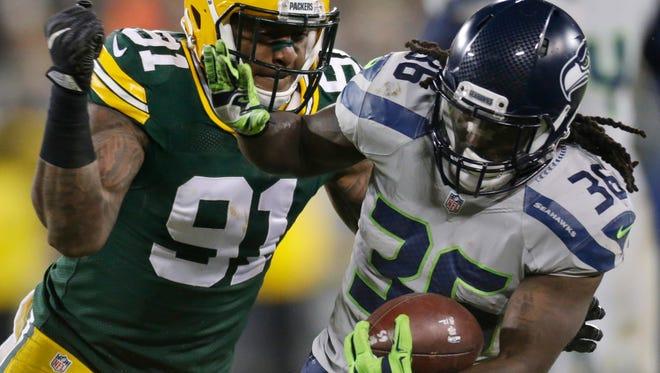 Green Bay Packers linebacker Jayrone Elliott (91) tackles Seattle Seahawks running back Alex Collins  after a 13-yard reception.