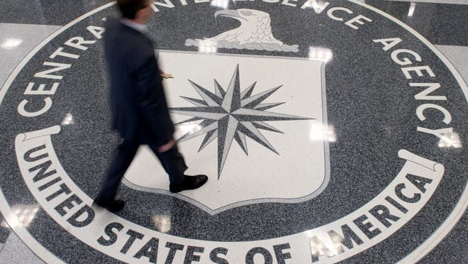 """(FILES) This August 14,2008 file photo shows a man as he crosses the Central Intelligence Agency (CIA) logo in the lobby of CIA Headquarters in Langley, Virginia. The director of the CIA insisted December 9, 2014 that US agents' use of brutal interrogation techniques against Al-Qaeda suspects helped prevent attacks, in the wake of a critical Senate report. John Brennan admitted that mistakes had been made, but said the Central Intelligence Agency's own review found that harsh interrogations """"did produce intelligence that helped thwart attack plans, capture terrorists and save lives."""" AFP PHOTO/SAUL LOEBSAUL LOEB/AFP/Getty Images"""