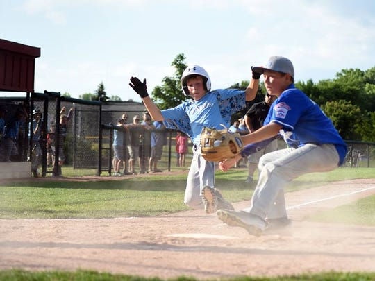 Glendale Little League player Braeden Ott slides into home plate in a game in July 2016.