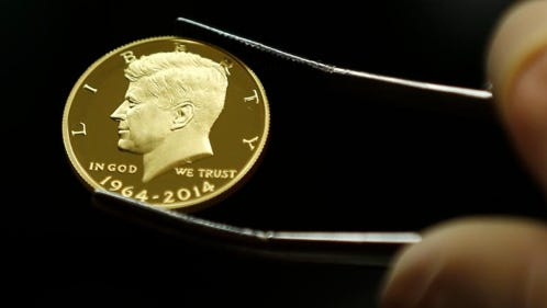 A newly-stamped gold coin of President John F. Kennedy is examined at the U.S. Mint at West Point on Tuesday, July 22, 2014, in West Point, N.Y. Kennedy is getting a new look on the new coin that is being made by the mint to mark the 50 years since the slain president debuted on a half-dollar. (AP Photo)