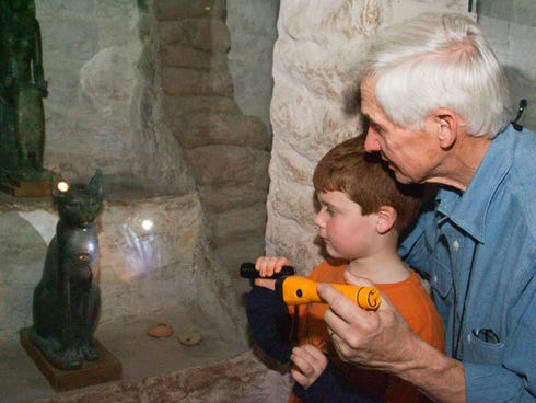 A grandfather and grandson explore the Field Museum's Inside Ancient Egypt exhibit on a flashlight tour as part of a family overnight at the museum.