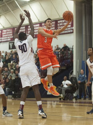 Cherokee's Zach Rowe, 3, takes the ball to the basket against Eastern's Onye Okoro, 40, during the second quarter of Tuesday's game.