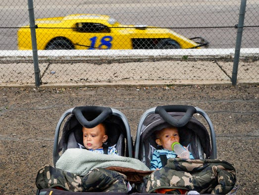 Twins, Terrence and Terrelle Dow, sit in the front row of the family section as Ed Vecchiarelli Sr, #18, races by in a Grand American Modified race at Colorado National Speedway Saturday, June 7, 2014, in Dacono, CO.