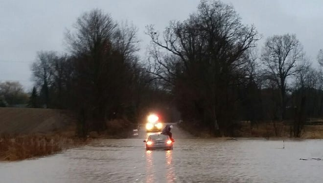 A man sits on top of his car surrounded by water.
