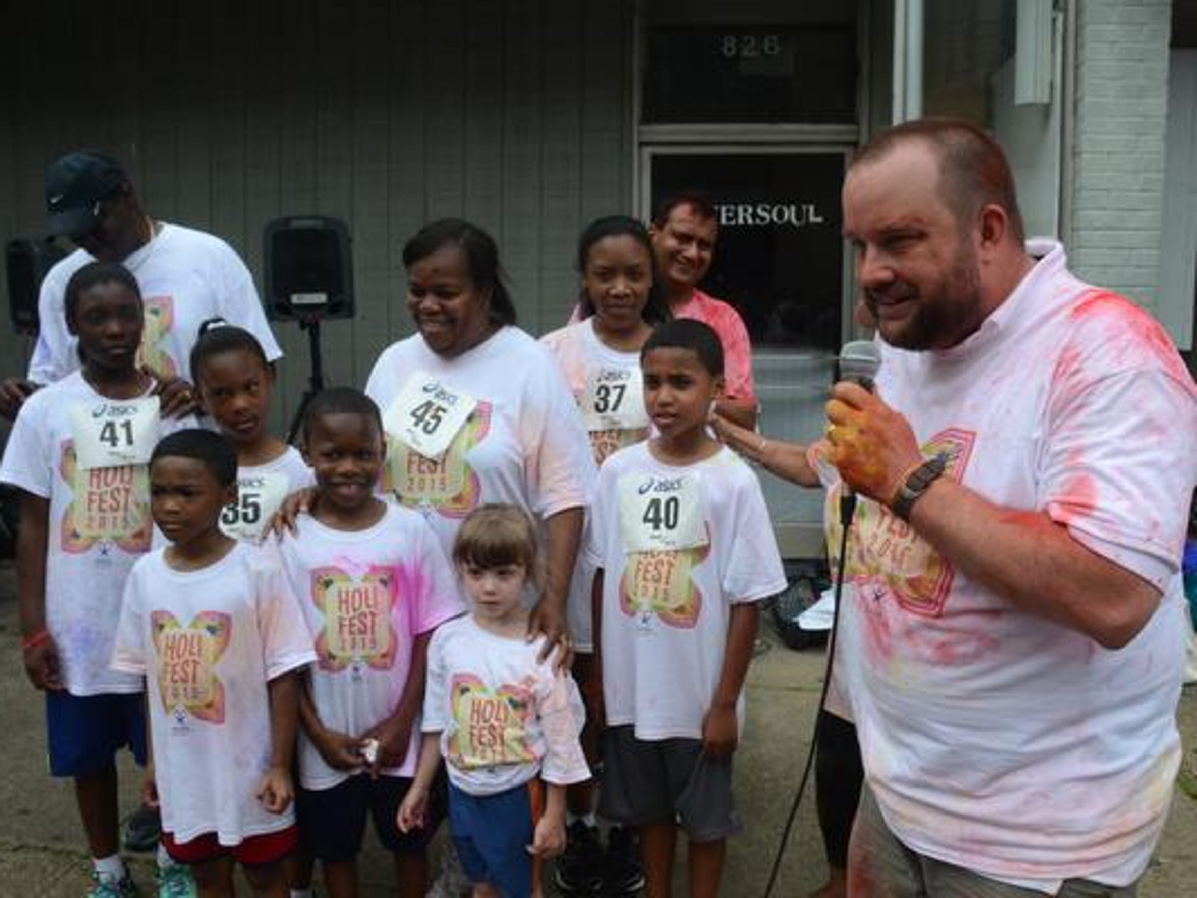Wade Bond (far right), executive director of the Rapides Children's Advocacy Center Inc., introduces Renee and Ronnie Gillam and their seven adopted children Saturday at the Holi Festival, a fundraiser for the group, in downtown Alexandria. The Gillams came into contact with CASA, a program of the organization, through the children.