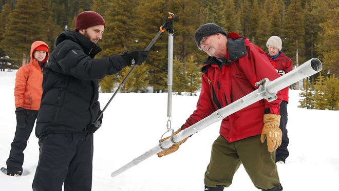Frank Gehrke, right, chief of the California Cooperative Snow Surveys Program for the Department of Water Resources, checks the weight of the snow sample on a scale held by Mikel Shybut, a policy fellow with the California Council on Science and Technology, during the second manual snow survey of the season at at Phillips Station on Thursday near Echo Summit.