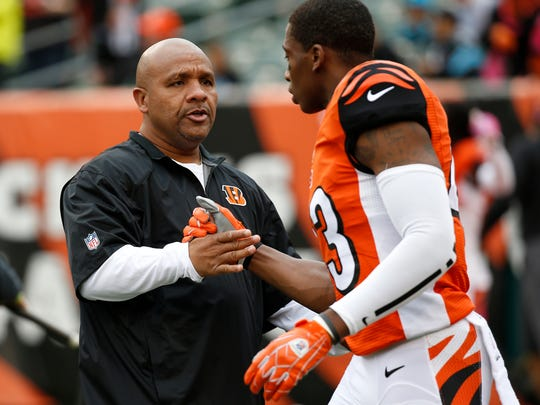 Bengals offensive coordinator Hue Jackson greets strong safety George Iloka on Oct. 12.